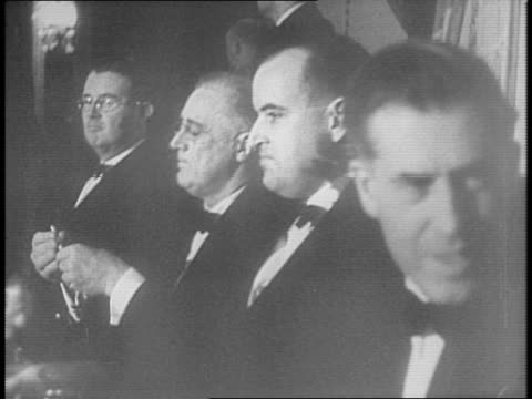 Banquet hall fills with guests / dignitaries in formal dress sit at banquet tables and in audience including Wendell Willkie Navy Secretary Frank...