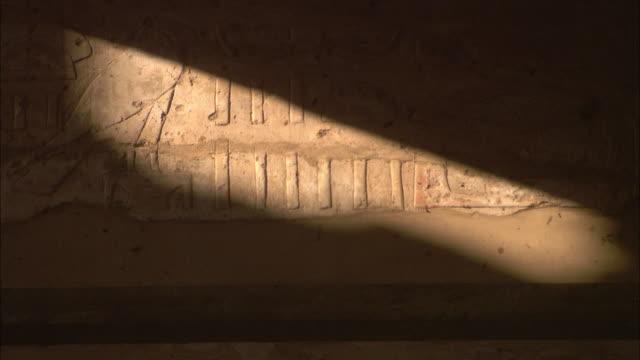 A bar of sunlight illuminates carvings in Egypt's Karnak Temple.