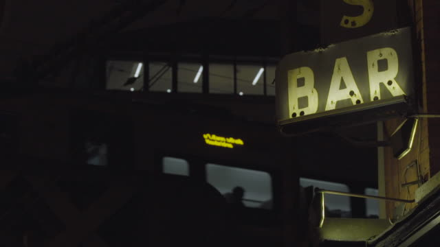 WS bar sign, corner bar in city, with elevated train lights passing in back, U.S. / Europe / Ireland / Dublin