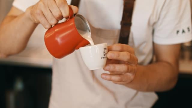 Bar tender gieten melk in de koffie
