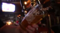 A bar tender pours a glass of Miller High Life beer at a bar on October 9 2015 in New York City Budweiser's parent company AB InBev is attempting to...