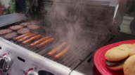 Barbecue gas grill with hamburgers and hotdogs cooking.