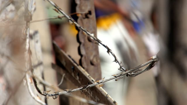 CU Barbed wire/ people in background / Diepsloot/ South Africa