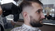 Barber hands cutting hair with electric razor at a barber shop