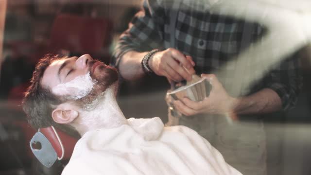Barber in Gentlemans Barber shaving client