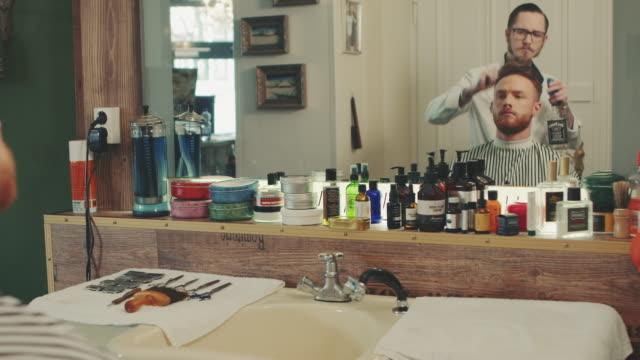 Barber preparing man for haircut