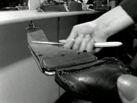 A barber sharpens her razor blade on a leather strap