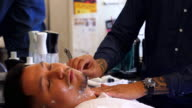 MS TD Barber shaving client with straight razor in barber shop