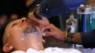 MS CU Barber shaving client with straight razor