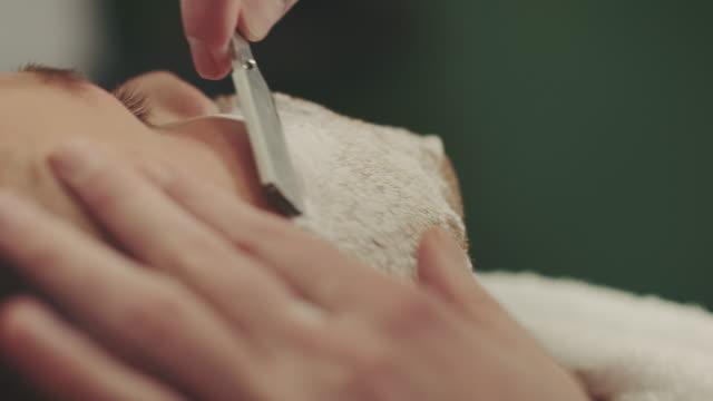 Barber shaving mans beard