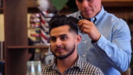 MS Barber styling clients hair after hair cut in barber shop