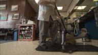 MS LA Barber sweeping up hair off floor at barber shop / Rutland, Vermont, USA