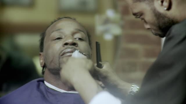 CU SELECTIVE FOCUS SHAKY Barber trimming customer's facial hair at barbershop, Brooklyn, New York City, New York State, USA