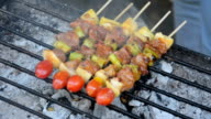 Bar-B-Q or BBQ cooking. Coal grill of pork skewers with tomatoes, pineapple and peppers.