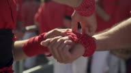 Barcelona castellers man hands dressing up with traditional costume