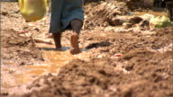 Barefoot male in long shorts carrying something in plastic grocery sack walking up muddy street sinking in red clay mud above ankles Storm damage...