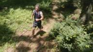 Barefoot man running across a forest path