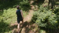 PAN Barefoot man running on a forest path