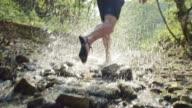 SLO MO Barefoot runner running across a creek in sunshine