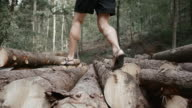 SLO MO DS Barefoot runner running across astack of logs in the forest