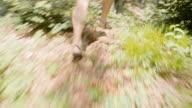 TS Barefoot runner running across forest undergrowth