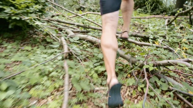 SLO MO TS Barefoot runner running in forest undergrowth