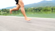 Barefoot running on road in the park with mountain background