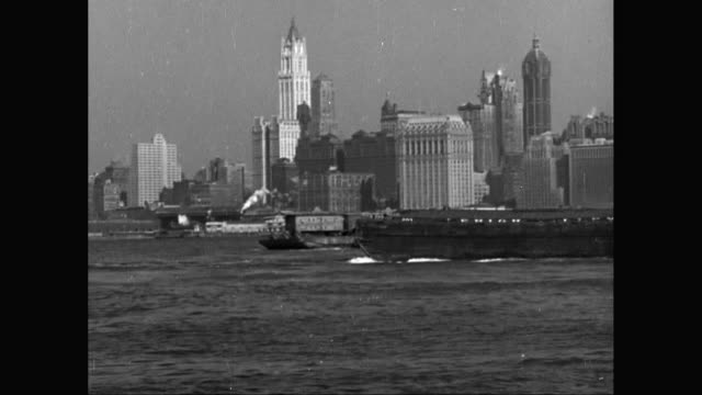 WS PAN Barge moving in Hudson River, Lower Manhattan cityscape in background / United States