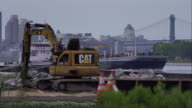 Barge passes by construction machinery in background along the East River.