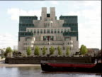 Barge passes in front of post-modernist MI6 building on banks of River Thames Vauxhall