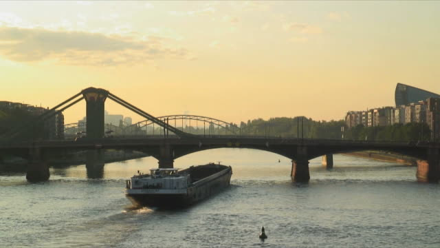 WS Barge passing under Ignatz Bubis Bridge on river Rhine at sunset, Frankfurt am Main, Germany