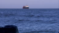 A barge sails just off the English coast where waves lap against a seawall. Available in HD.