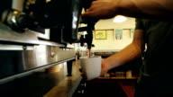 Barista in local coffee shop preparing fresh hot beverage for customer