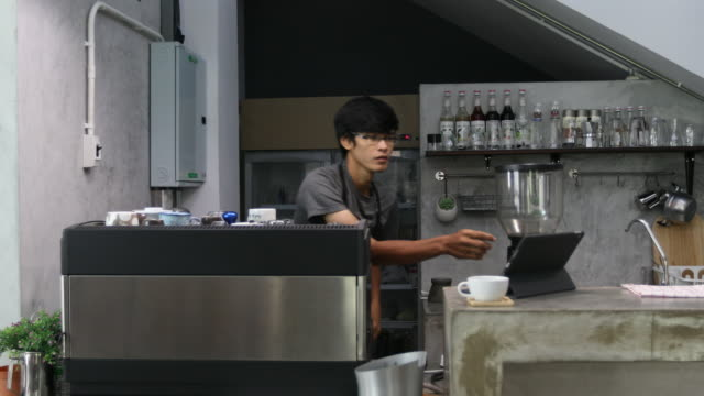 Barista makes a cup of coffee for the visitor