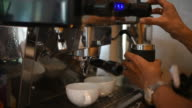 Barista making two of coffee latte in coffee bar.