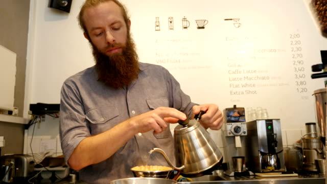 Barista warm water gieten in dripper in café