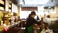 Baristas work behind the counter inside a Starbucks Coffee Korea Co store in Gimpo South Korea A female barista cleans untensils and prepares coffee...