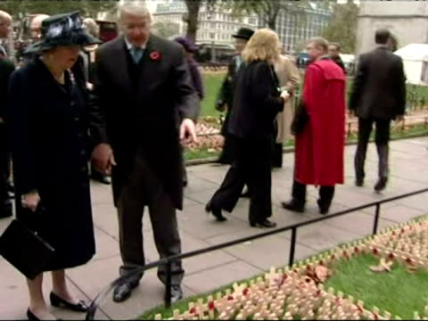 Baroness Margaret Thatcher accompanied by John Major looks at Remembrance Day crosses and Wreaths outside Westminster Abbey