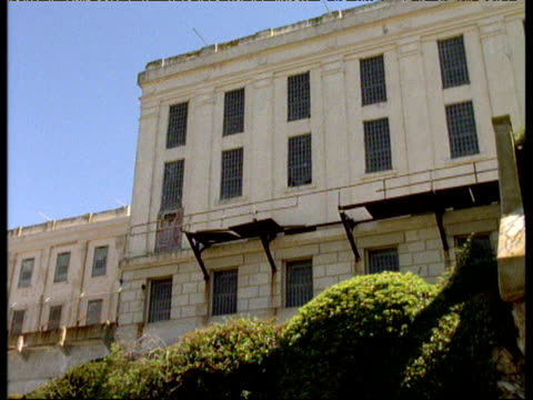 Barred windows of Alcatraz prison pan left and tilt down exterior of building to flowers in foreground San Francisco