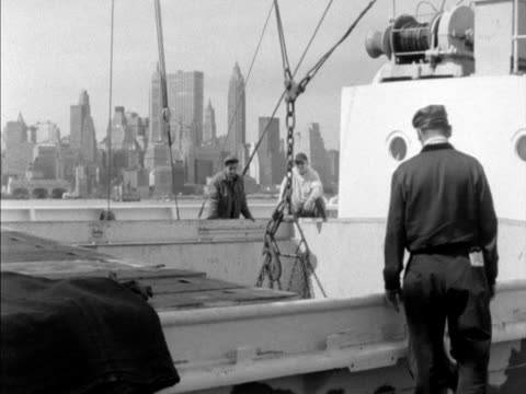Barrels are unloaded from a ship at the docks in New York City