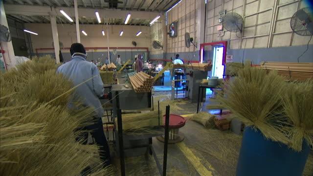 Barrels of unbound straw brooms Black male prisoner in safety mask working at prison workstation w/ stack of round wooden handles using hammer on...