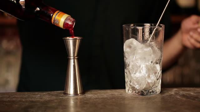 Bartender adding campari to cocktail