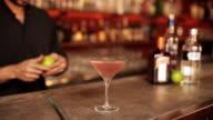 Bartender adding lime peel garnish to cosmopolitan