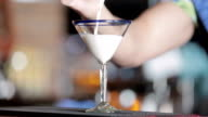 Bartender filling martini glass with bailey's irish cream