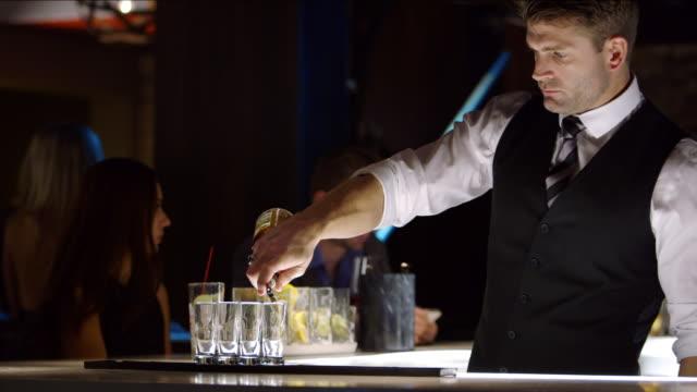 WS bartender poring liquid into shot glasses