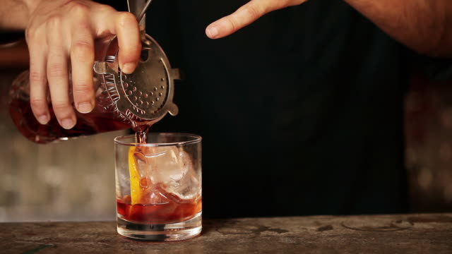 Bartender pouring cocktail into glass