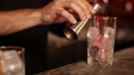 Bartender pouring contents of jigger into cocktail glass