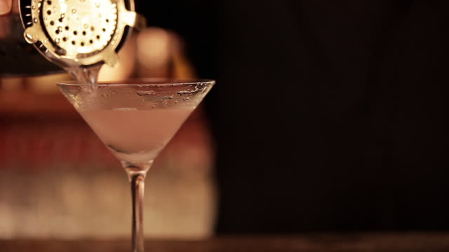 Bartender pouring cosmopolitan cocktail, close-up
