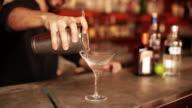 Bartender pouring cosmopolitan