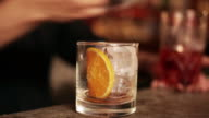 Bartender pouring negroni into glass